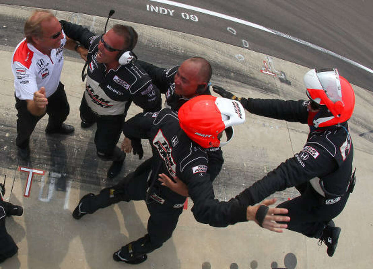 The pit crew for Helio Castroneves, driver of the #3 Team Penske Dallara Honda, celebrates his victory during the IRL IndyCar Series 93rd running of the Indianapolis 500.