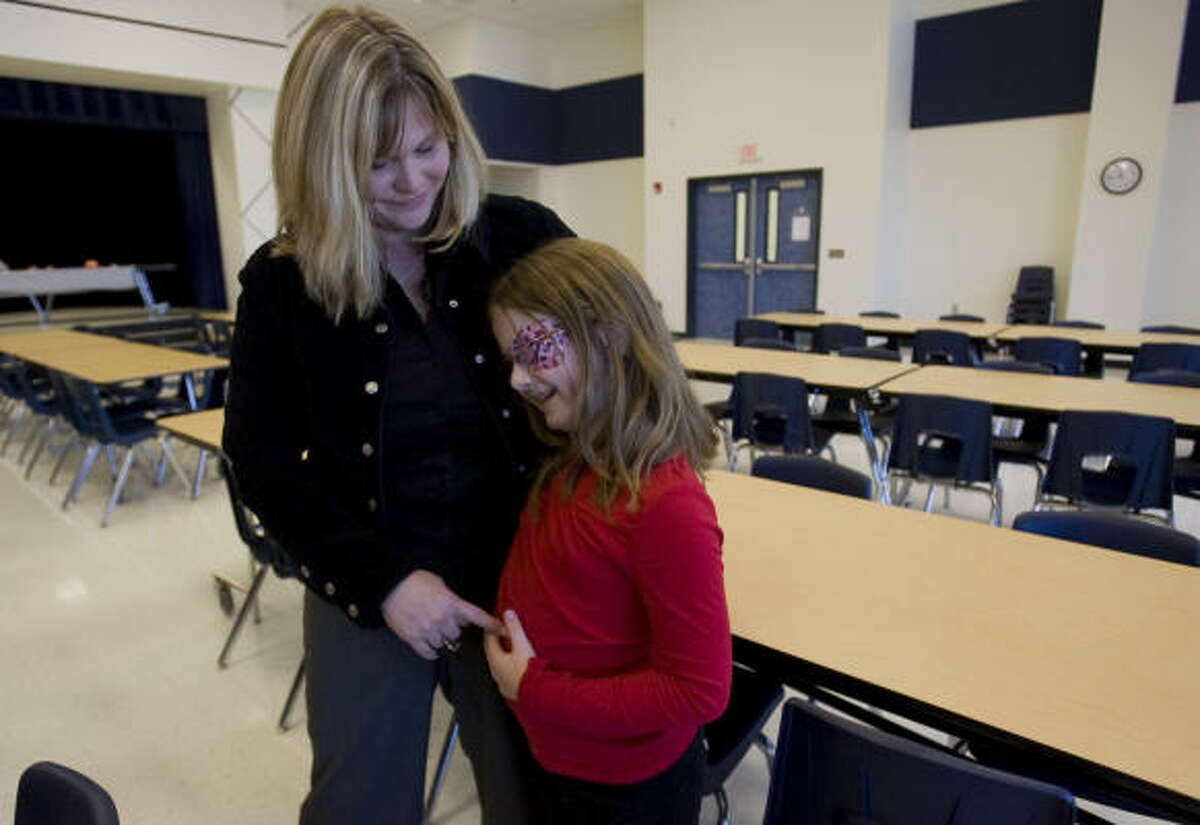 English teacher Catherine Jackson-Prieur spends a moment with her daughter Caitlyn Jackson, 8, during lunch at Crenshaw Elementary and Middle School on the Bolivar Peninsula on Wednesday.