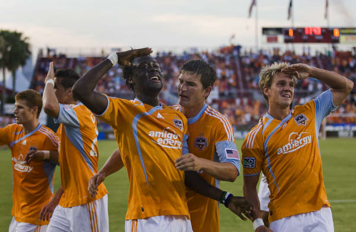 Dynamo forward Kei Kamara, center, salutes the crowd with teammate Stuart Holden, right, as Andrew Hainault joins the celebration of Kamara's first half goal.