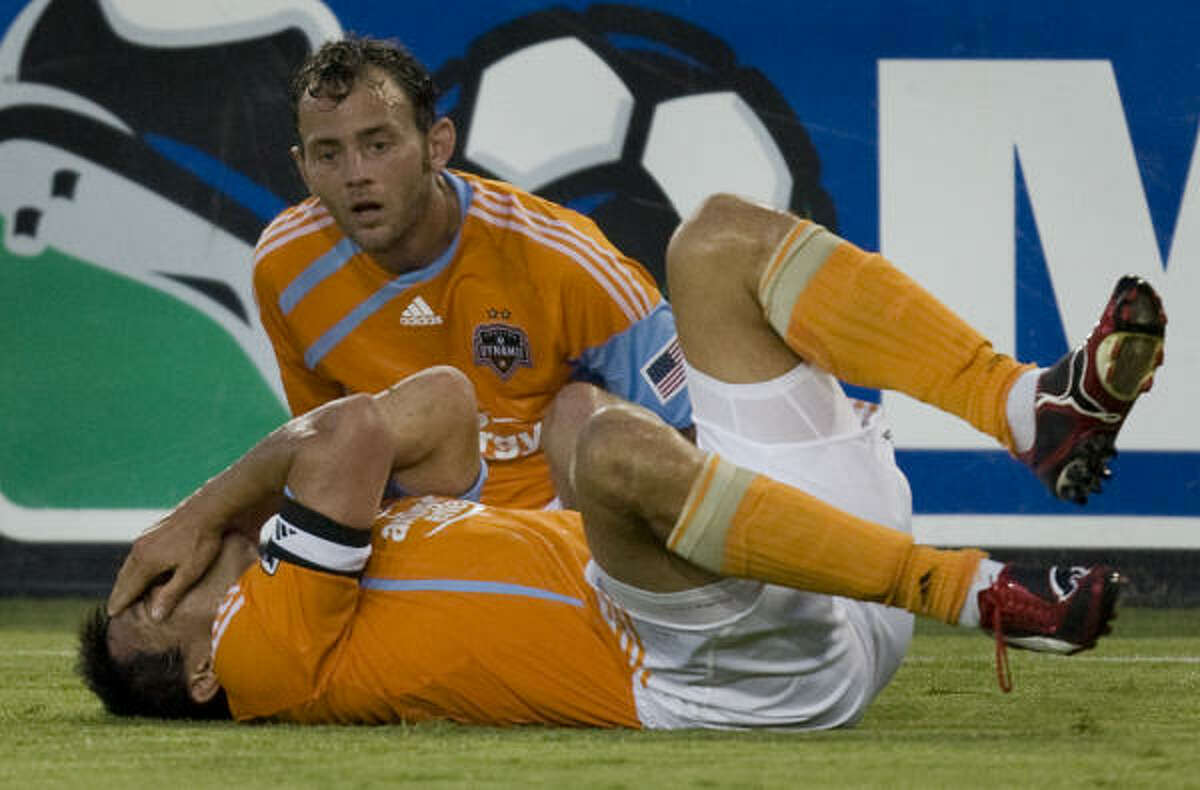 Dynamo forward Brian Ching collapses on the turf after being hit in the face during the first half.