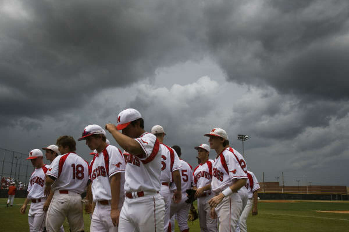 Memorial players walk off the field as storm clouds threaten the day's action.
