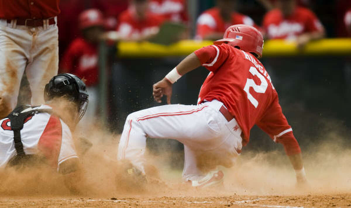 Bellaire's Jarrett Higgins beats the tag at the plate by Memorial catcher M.P. Cokinos after stealing home in the fifth inning.