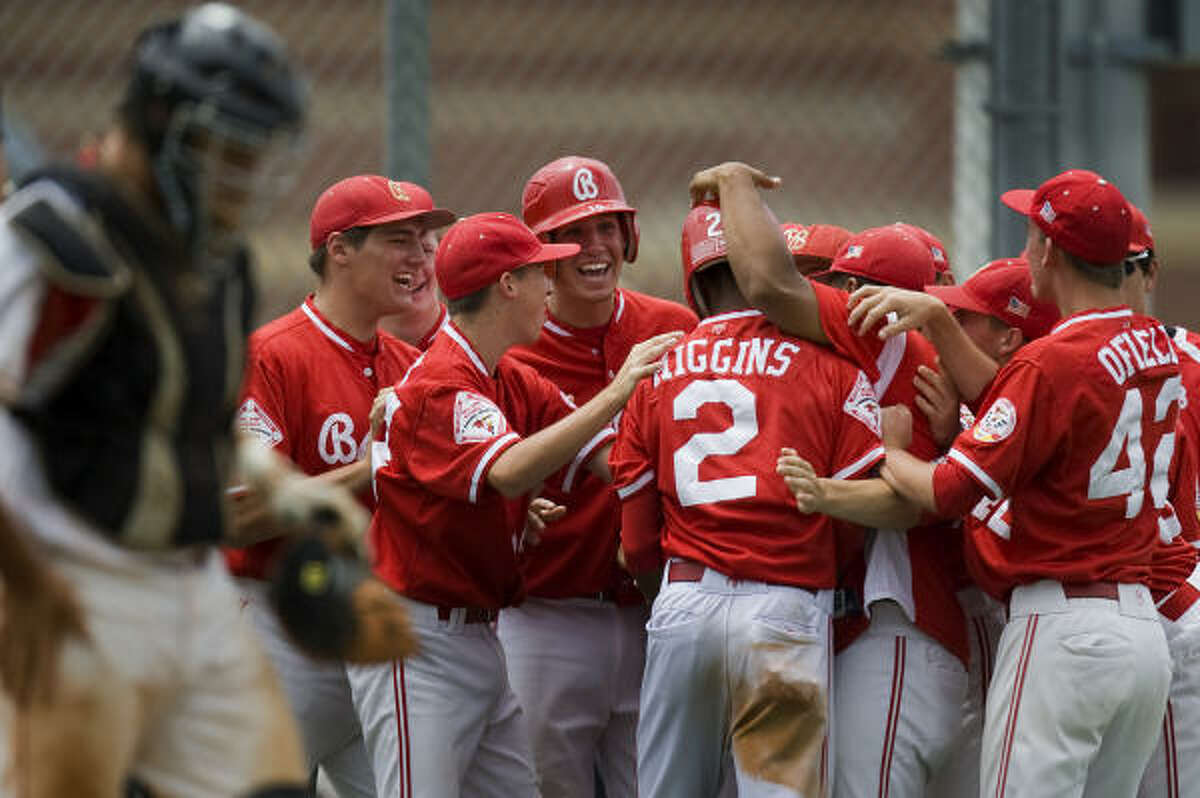 Bellaire's Jarrett Higgins is mobbed by teammates after his steal of home.