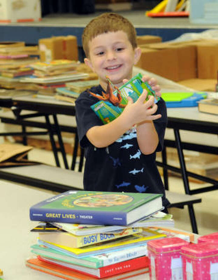 Galveston ISD - $62 millionEnrollment: 6,695Debt outstanding per student: $9,376Pictured: Chase Oats, 5, shows off a book he found while sorting through books that were donated to the Galveston ISD. Photo: Kim Christensen, For The Chronicle