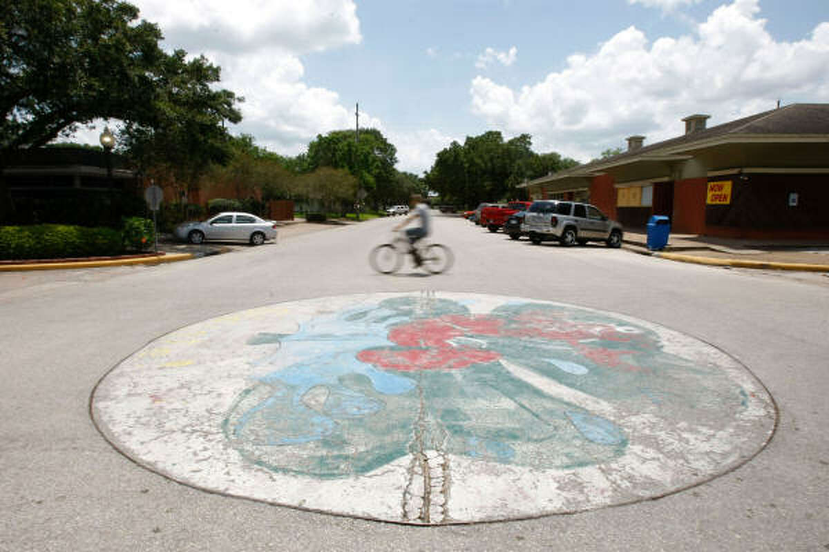 A man rides his bike pass a decorative painting at Fifth and Cooper in downtown Brookshire.