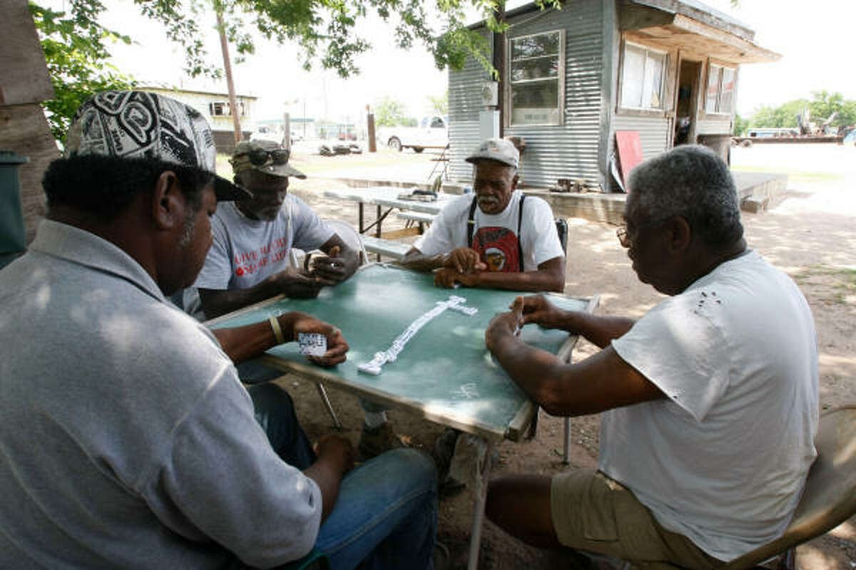 Friends Don Gillum, John Irving, L.B. Bingles and a man who declined to be identified play dominoes in Hempstead. The federal cases have cast a shadow on life in Waller.