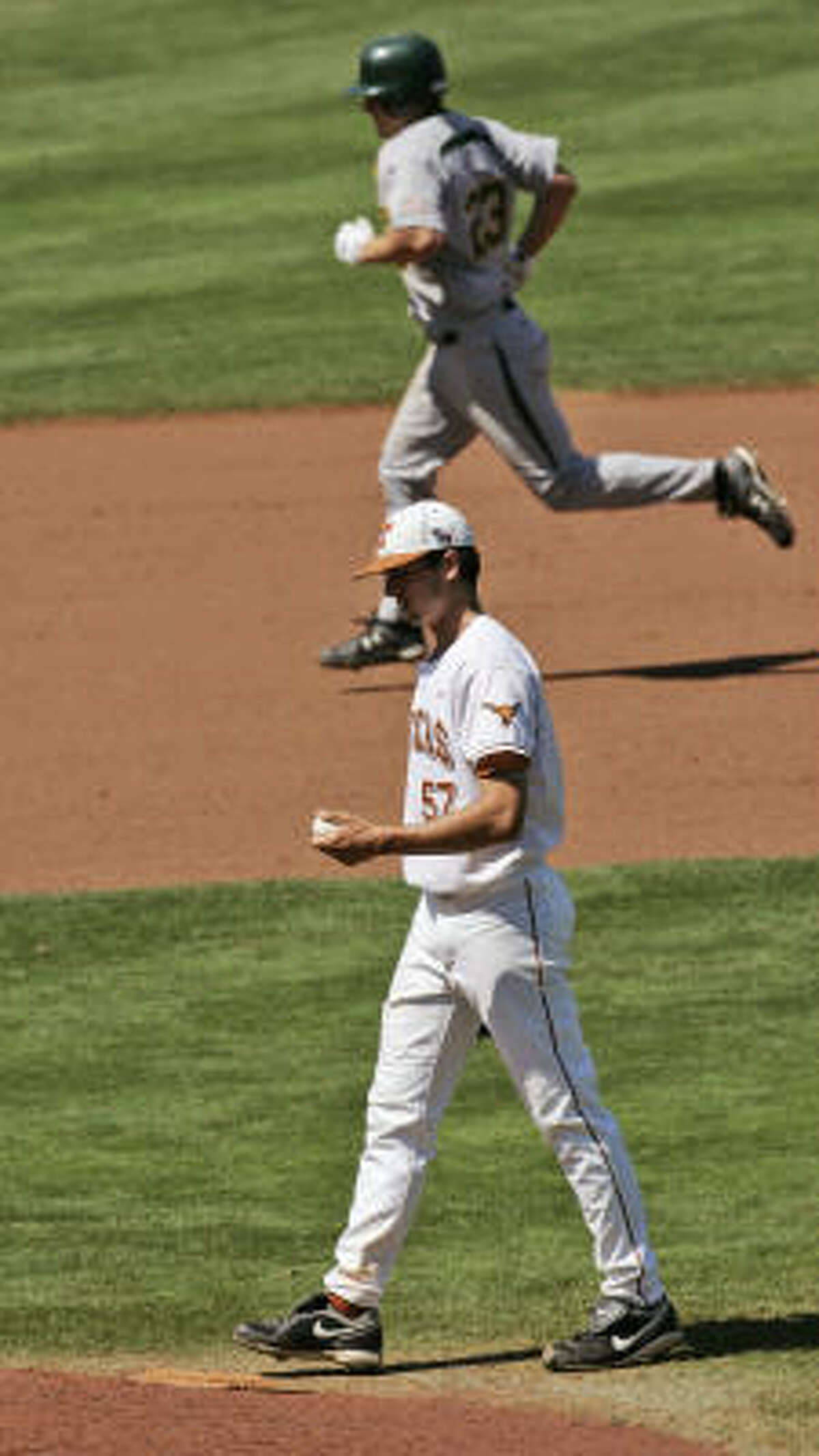Texas pitcher Andrew McKirahan walks back to the mound as Baylor's Dan Evatt rounds the bases behind him following a ninth-inning home run. The Bears beat the Longhorns 14-9 in the Big 12 tournament opener in Oklahoma City.