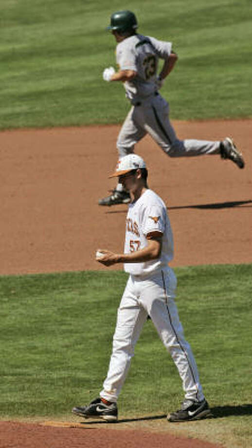 Texas pitcher Andrew McKirahan walks back to the mound as Baylor's Dan Evatt rounds the bases behind him following a ninth-inning home run. The Bears beat the Longhorns 14-9 in the Big 12 tournament opener in Oklahoma City. Photo: AP