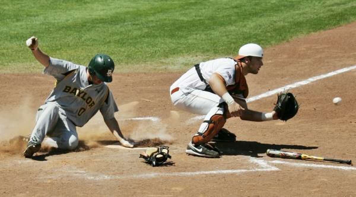Baylor's Ben Booker slides safely into home plate behind Texas catcher Cameron Rupp in the seventh inning.