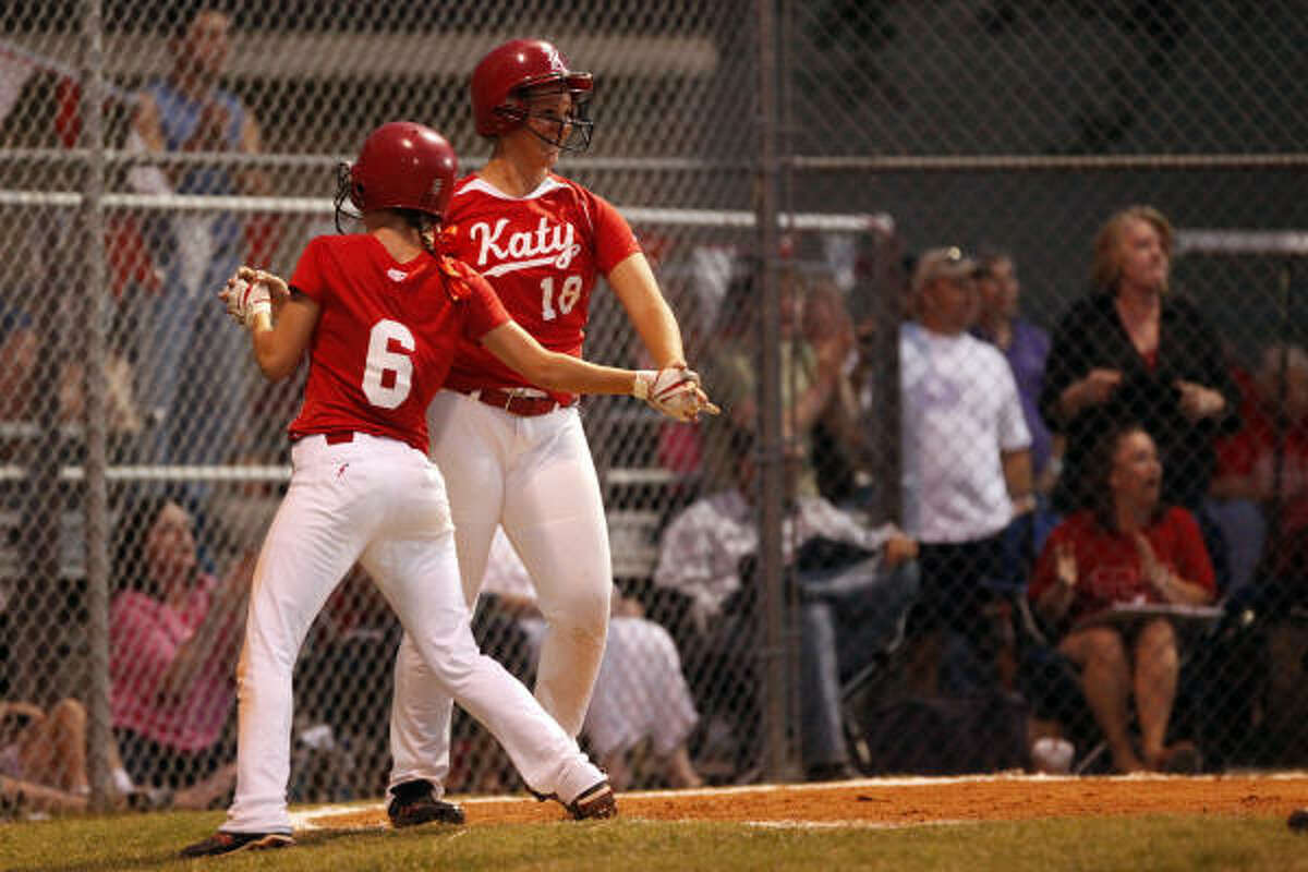 Katy's Melissa Herman (18) congratulates teammate Darian Blake (6) as Blake comes in to score a run.