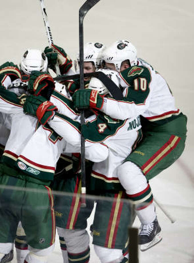 Aeros' Tony Hrkac (14) is mobbed by his  teammates after scoring the winning goal in the second overtime. Photo: Bob Levey, For The Chronicle
