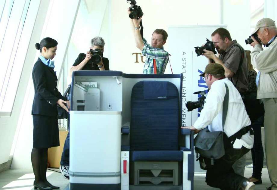 Photographers take photos of mock-up of an international business class seat. Photo: JOSHUA TRUJILLO / SEATTLEPI.COM