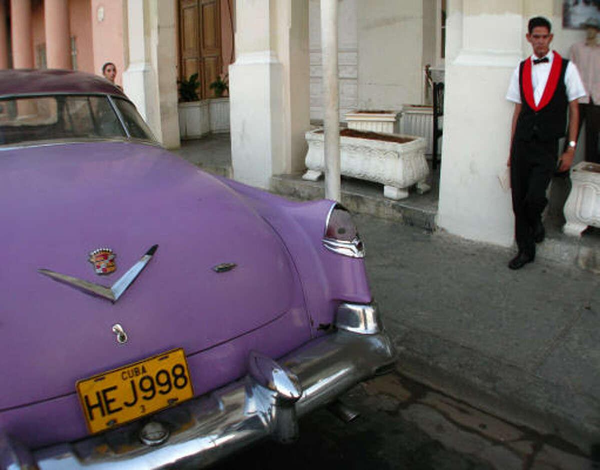 A classic 1950s Cadillac is strategically parked in front of a cafe on the tree-lined Prado to attract clients.