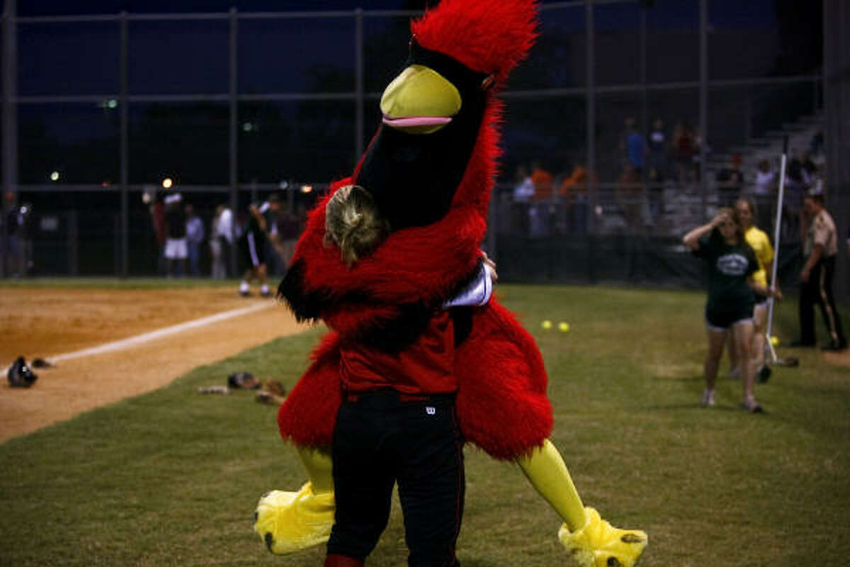 Bellaire's Mackenzie Sher gets a hug from Kelly the Cardinal after Bellaire's win Tuesday.