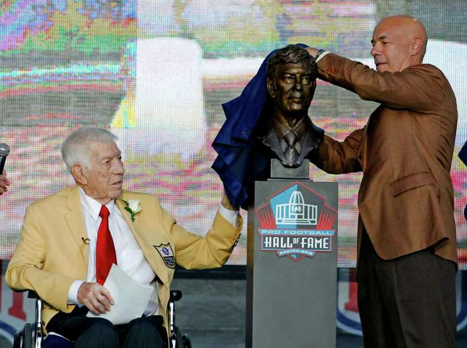Ed Sabol, left, looks on as his son, Steve, unveils a bust of Ed during the induction ceremony at the Pro Football Hall of Fame, Saturday, Aug. 6, 2011, in Canton, Ohio. (AP Photo/Ron Schwane) Photo: Ron Schwane, FRE / FR78273 AP