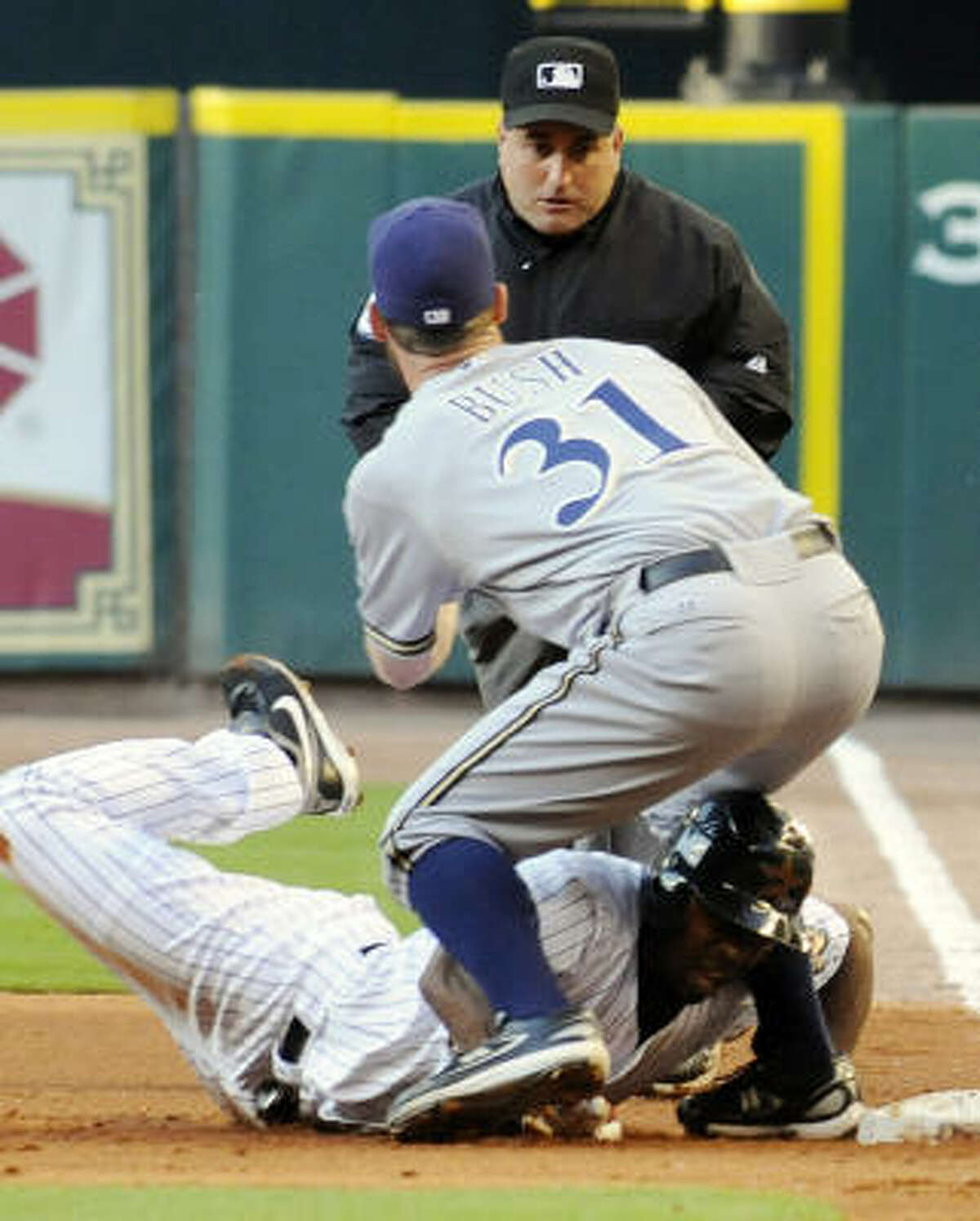 Houston Astros' Michael Bourn returns safely to first as Milwaukee Brewers pitcher Dave Bush shows the ball to first base umpire Eric Cooper in the first inning.