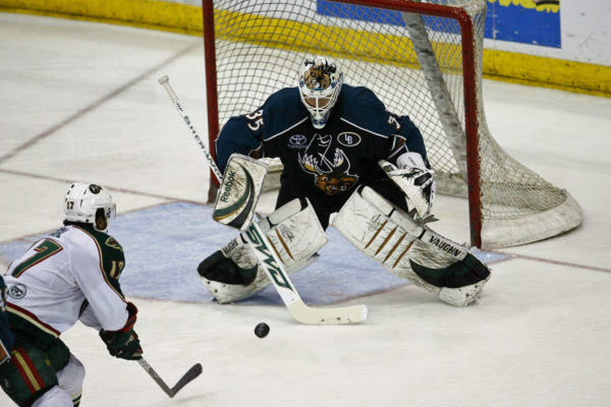 Houston's Robbie Earl (left) takes a shot on Manitoba goalie Cory Schneider during the second period.