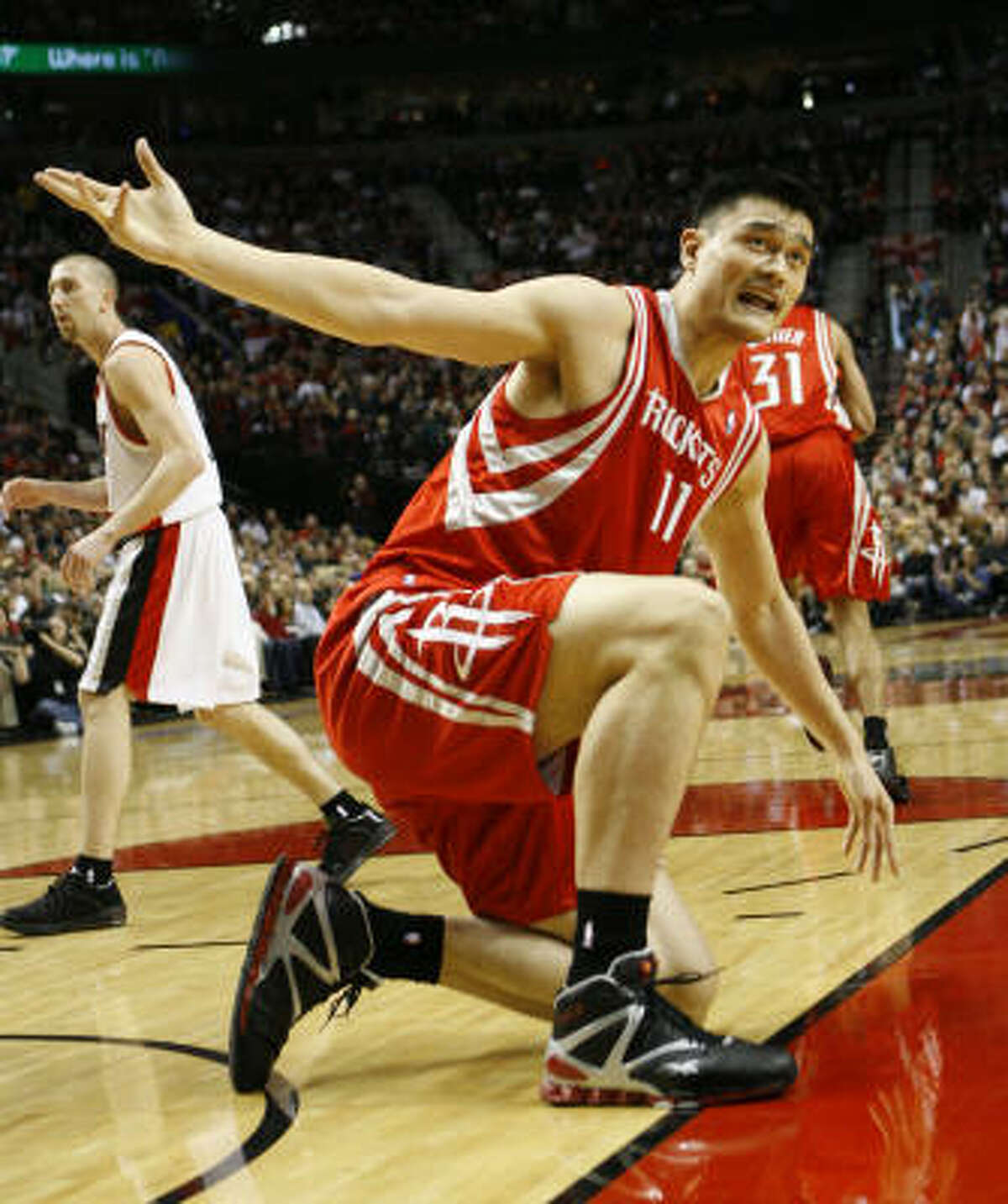 Rockets center Yao Ming (11) appeals to the ref after being knocked down by Portland Trail Blazers center Joel Przybilla (10) in the first quarter.