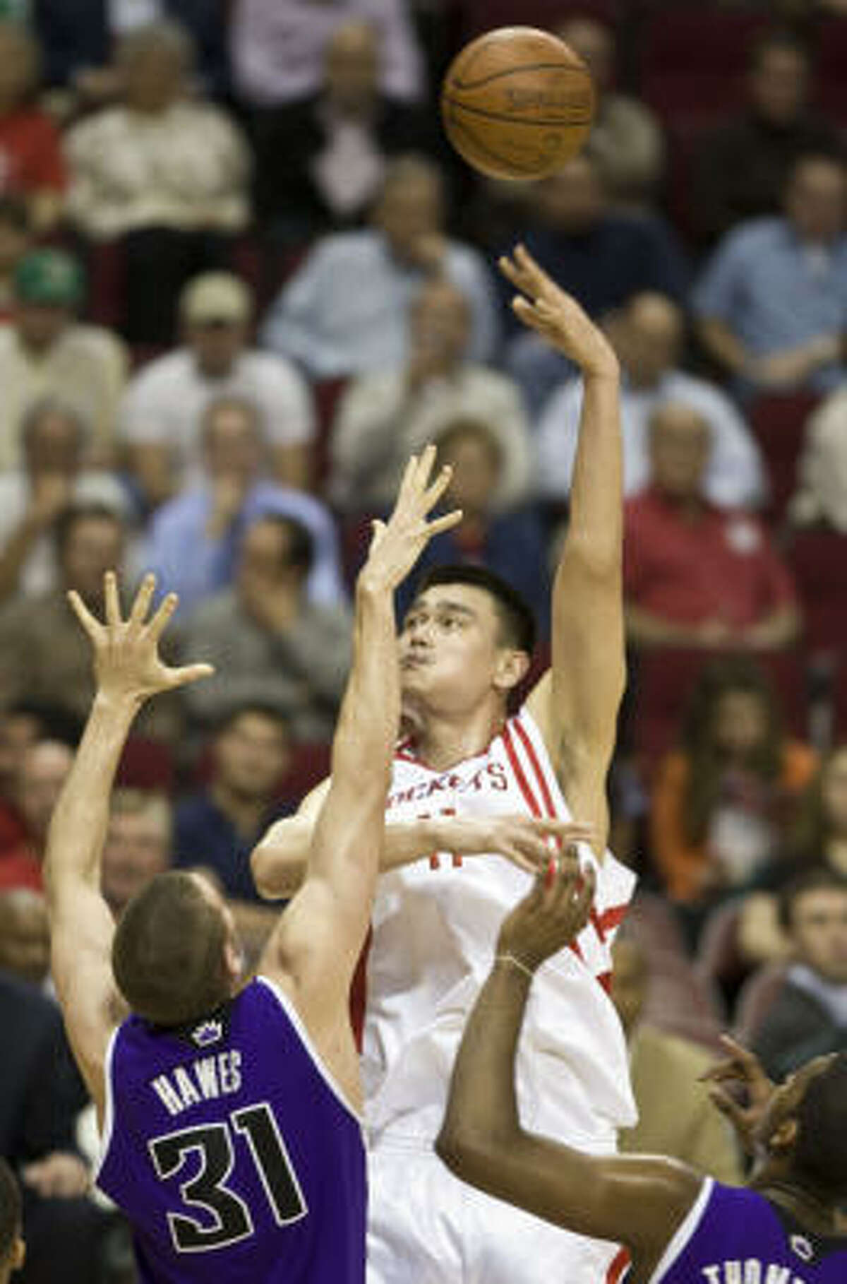 Yao Ming, center, shoots a sky hook over two defenders during first half.