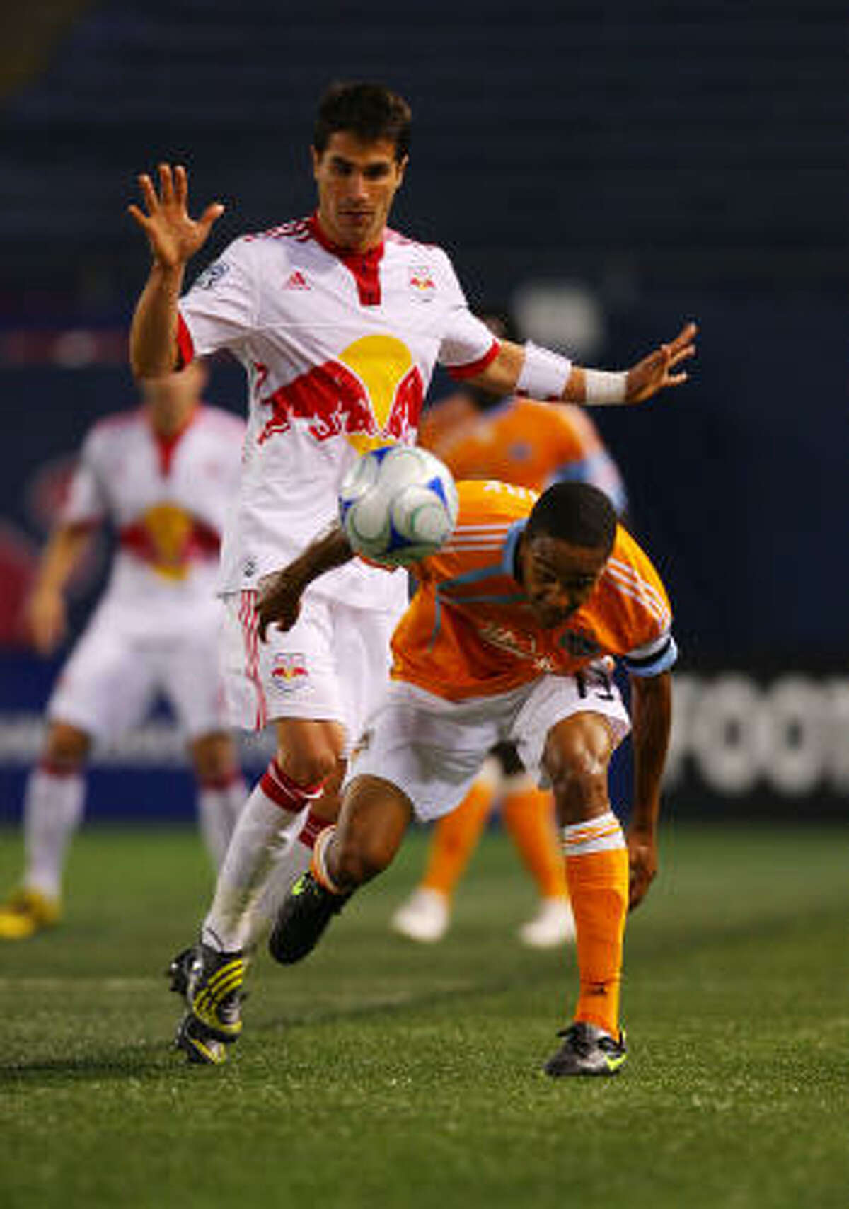 Ricardo Clark of the Dynamo and Juan Pablo Angel of the New York Red Bulls battle for the ball.