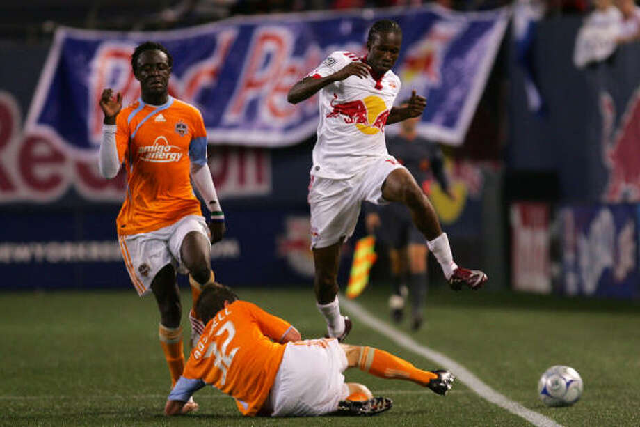 Macoumba Kandji of the New York Red Bulls jumps over Bobby Boswell of the Dynamo. Photo: Chris Trotman, Getty Images