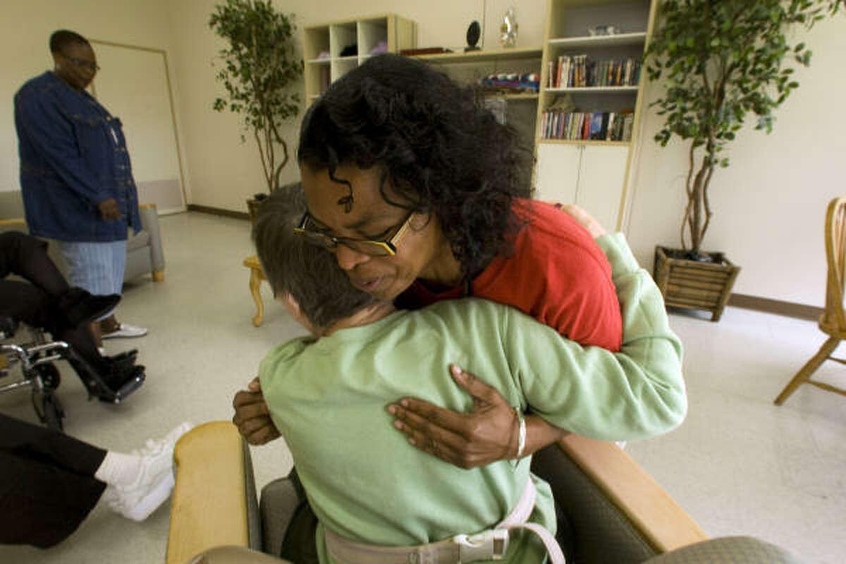 Magnolia Taylor, an employee at the Richmond State School, gets a hug from one of the school's residents, who his mentally retarded, while she was working in the Forever Young building that is dedicated to those ages 50 and older.
