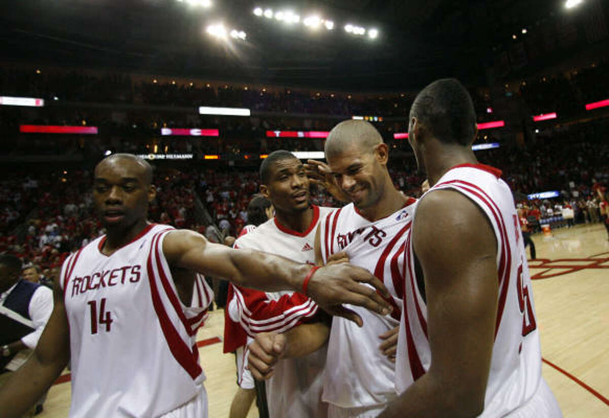 Rockets forward Carl Landry (14), Shane Battier, center, and Ron Artest walk off the court victoriously after beating the Lakers.
