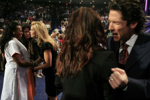Victoria and Joel Osteen pray with church members during a Lakewood service. Photo: Eric Kayne, Chronicle
