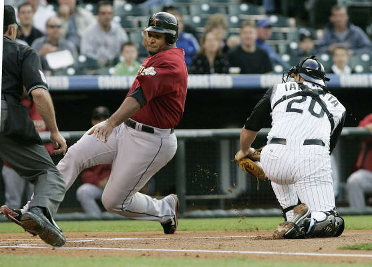 Houston's Carlos Lee moves around the tag of Colorado Rockies catcher Chris Iannetta to score in the first inning of Wednesday's game in Denver. The Astros won 15-11.
