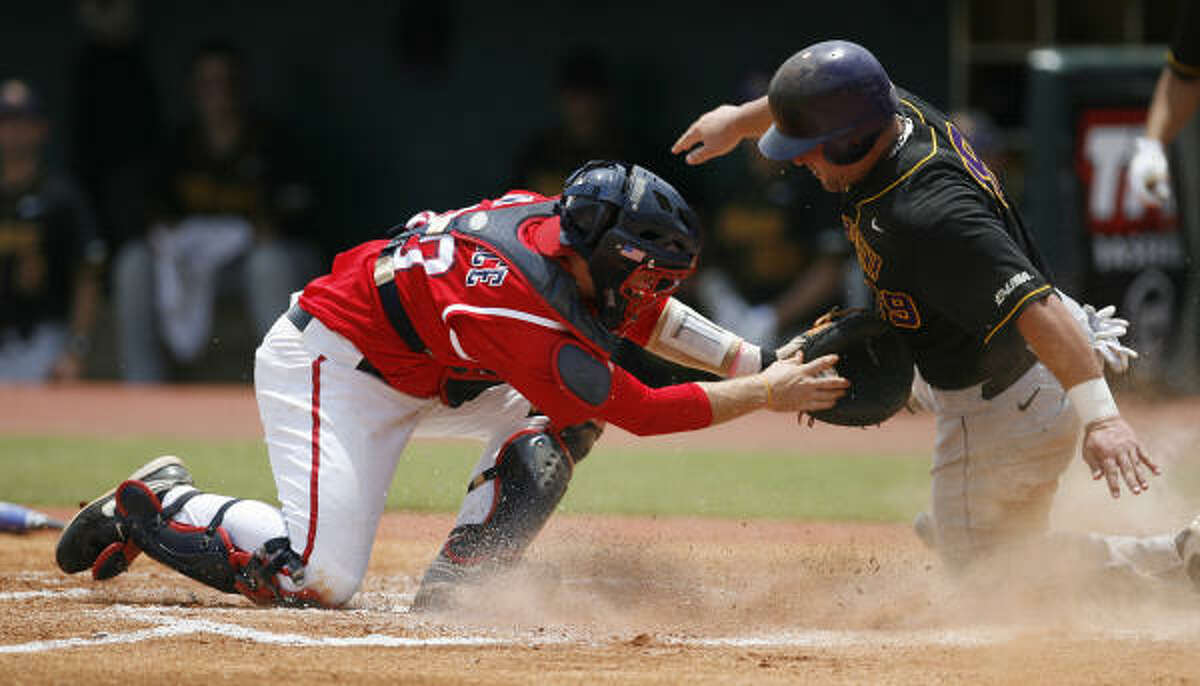 UH catcher Chris Wallace makes the tag at home plate to retire East Carolina's Kyle Roller in the first inning.