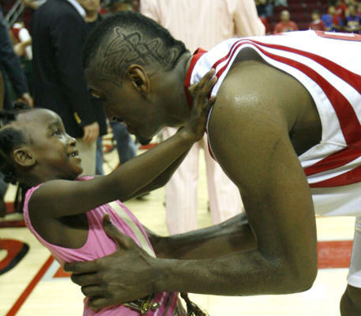Rockets forward Ron Artest reaches out to embrace his daughter, Diamond, after the Rockets beat the Los Angeles Lakers.