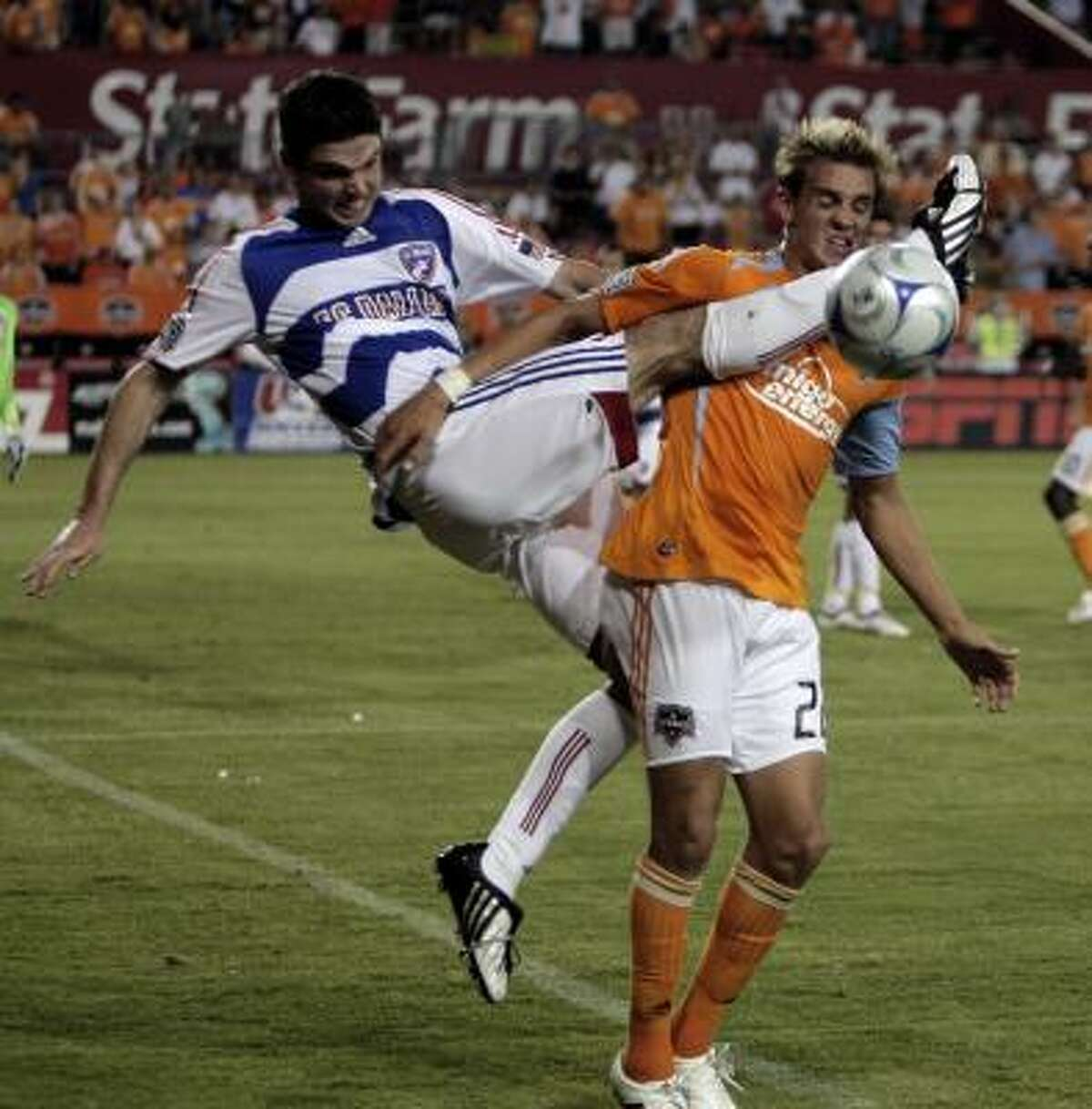 FC Dallas' Drew Moor, left, gets a leg up high on Houston's Stuart Holden in the first half of the Dynamo's 1-0 win Saturday.