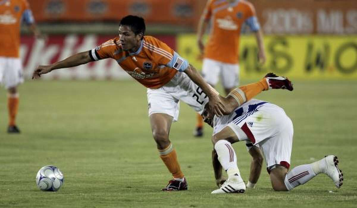 Houston's Brian Ching, left, leaps over FC Dallas' Steve Purdy in the first half of an MLS soccer game Saturday.