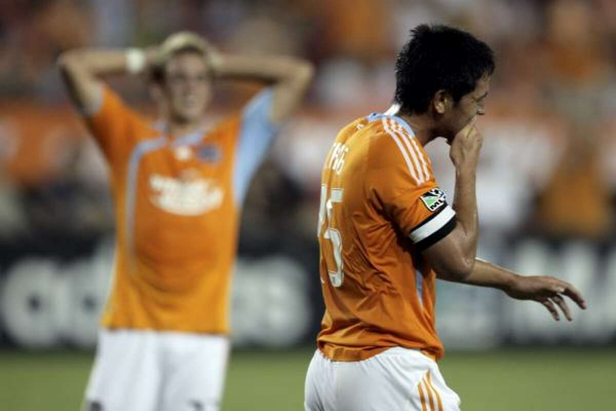 Houston forward Brian Ching, foreground, as well as Stuart Holden react to a missed scoring opportunity by Ching during the first half Saturday.