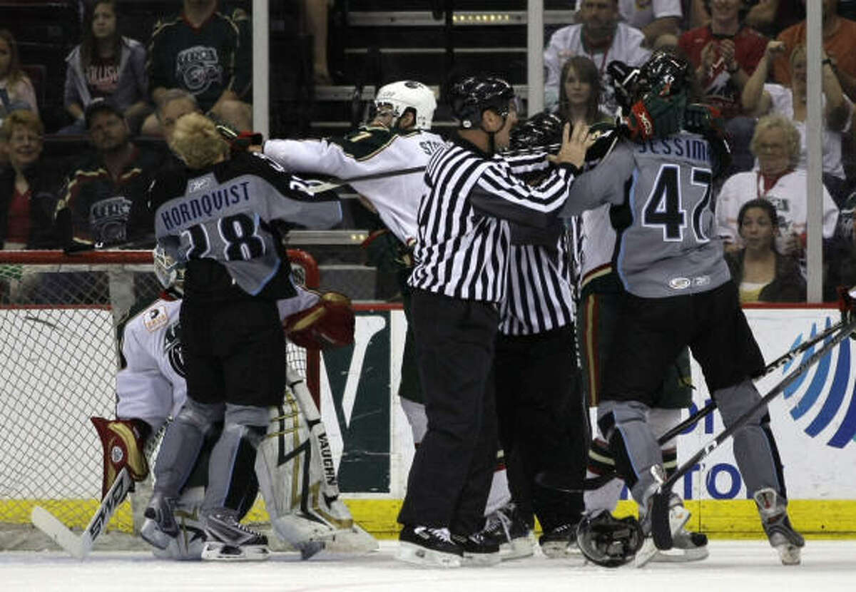 Tempers flair as referees separate Milwaukee Admirals and Houston Aeros players in front of the Aeros goal during the first period.