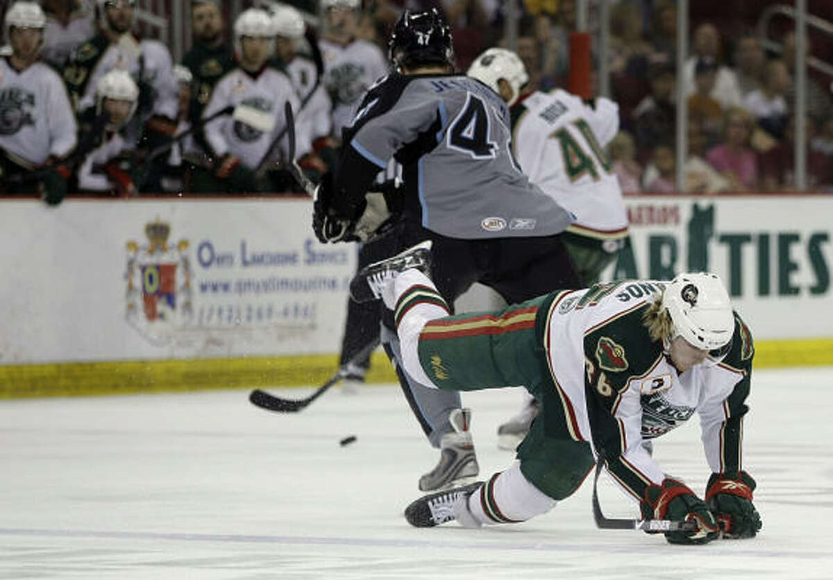 Aeros winger Krys Kolanos hits the ice after having the puck cleared by Milwaukee Admirals winger Hugh Jessiman during the first period.
