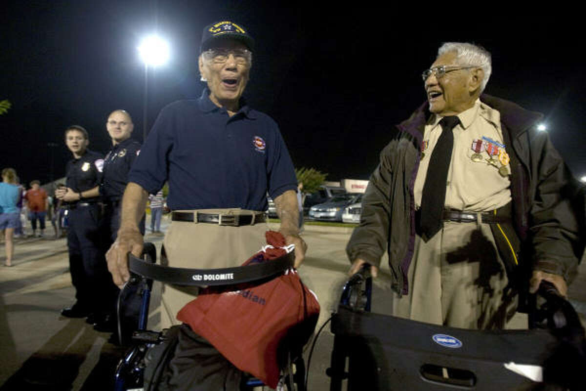 WWll veterans, George Orena, 90, and Marcos Barelas, 86 share a laugh in a shopping center parking lot in Conroe before departing for the airport to go on a Lone Star Honor Flight honoring more than 100 WWll veterans.