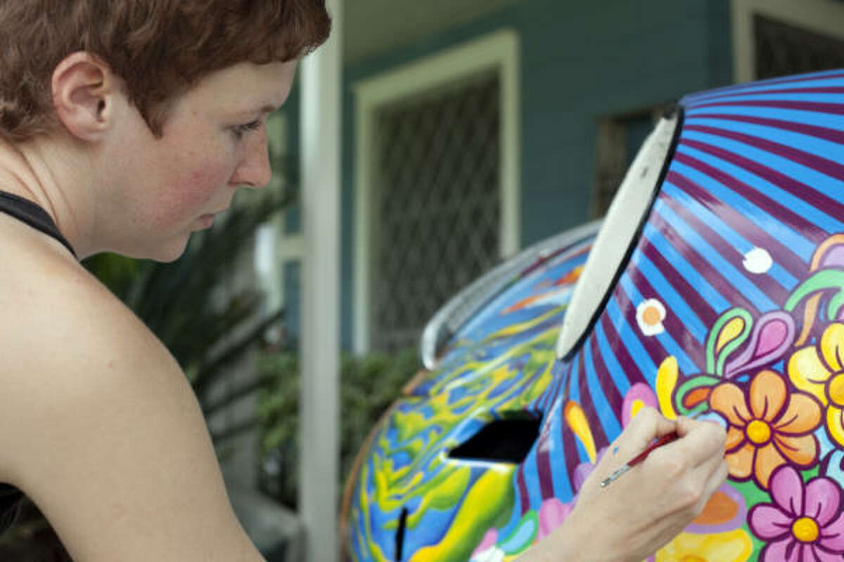 Robynn Sanders paints Psychedelic Surfer Dude, a restored 1963 Porsche 356B owned by David Duthu, in preparation for the upcoming 2009 Houston Art Car Parade.