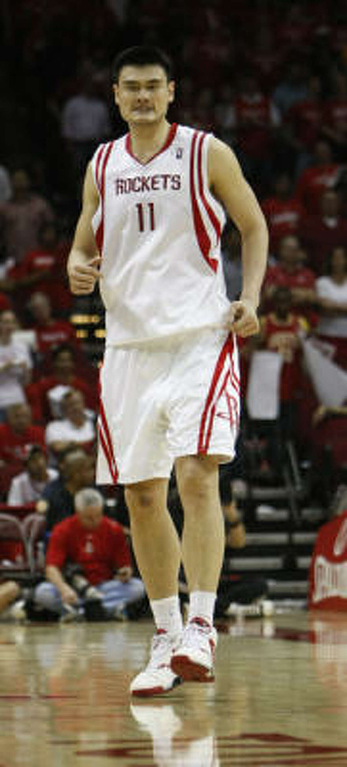 Yao Ming limps up court after hurting his ankle in the fourth quarter.