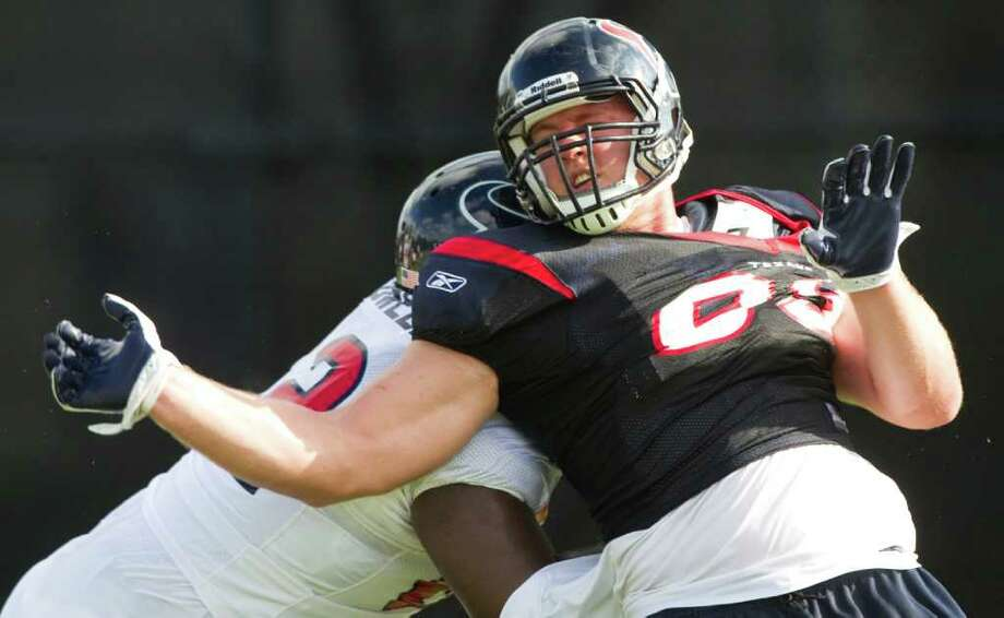 Houston Texans defensive end J.J. Watt, right, does a spin move as he goes through a pass rush drill against Houston Texans guard Antoine Caldwell during Texans training camp at the Methodist Training Center Wednesday, Aug. 3, 2011, in Houston.  ( Brett Coomer / Houston Chronicle ) Photo: Brett Coomer, Staff / © 2010 Houston Chronicle
