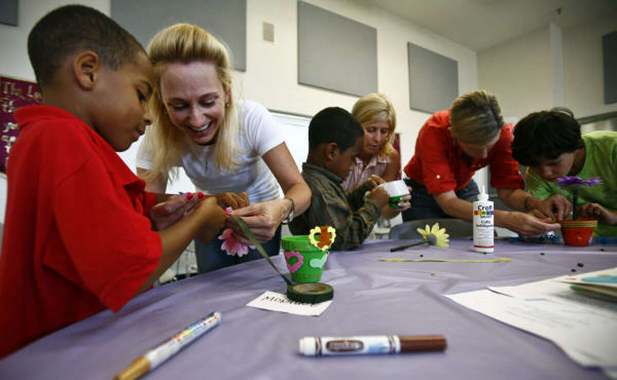 Elric Haynes gets help from volunteer Stef Levy while working on creating mother's day gifts during the Star of Hope