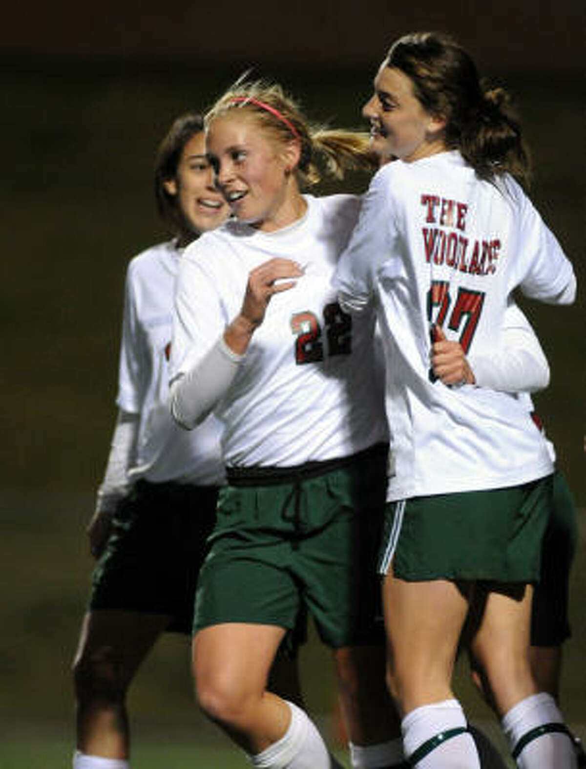 Olivia Kintigh, left, and her Highlander teammates celebrate a goal this past season.