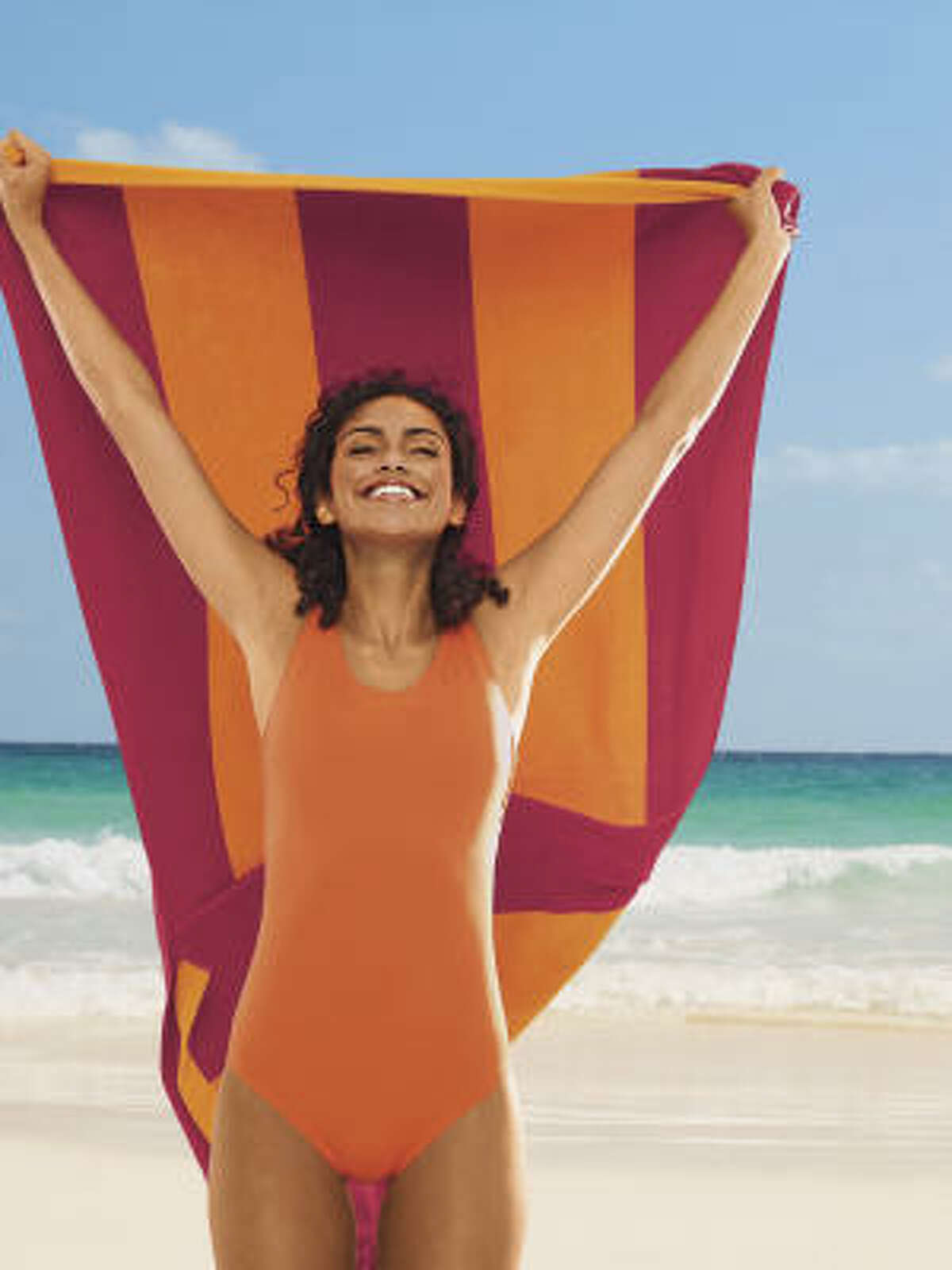 Tugless tank bathing suit, $39.50, and ruby stripe beach towel, $39.50, at Land's End.