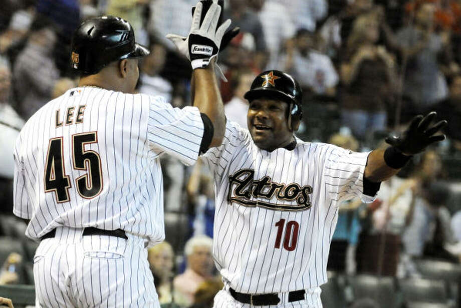 Houston's Miguel Tejada (10) is congratulated by teammate Carlos Lee after hitting a two-run home run, his first of the season, in the first inning of Thursday's game against the Chicago Cubs at Minute Maid Park. Unfortunately for the Astros, Tejada's homer wouldn't prevent them from falling 8-5. Photo: Pat Sullivan, AP