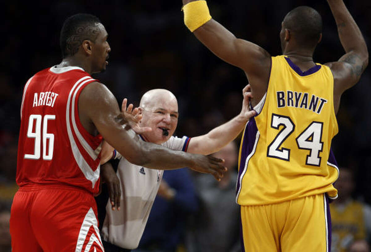 Los Angeles Lakers guard Kobe Bryant, right, and Rockets guard Ron Artest are separated by referee Joe Crawford. Artest was ejected from the game, but Bryant was later assessed a retroactive Flagrant Foul Penalty One.