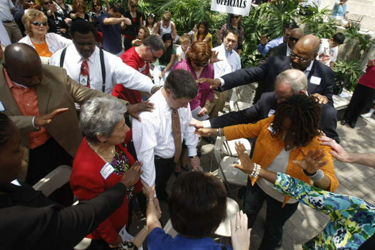 People pray for Harris County Judge Ed Emmett, center, and other judges present during the National Day of Prayer gathering at Hermann Square in front of Houston City Hall on Thursday.