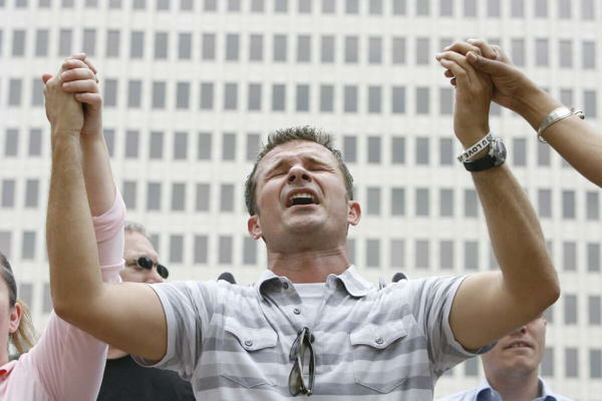 Mark Kubicek, of Humble, prays while holding the hands of Dorothy Hrnciar, left, and Vonda McTilbra during the National Day of Prayer gathering at Hermann Square in front of Houston City Hall on Thursday.