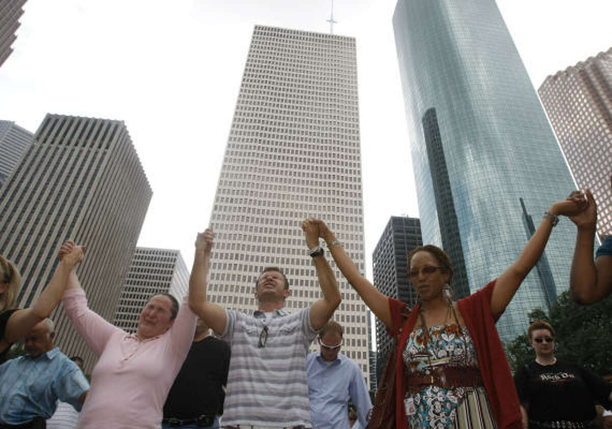 Dorothy Hrnciar, from left, Mark Kubicek, and Vonda McTilbra hold hands as they pray during the National Day of Prayer gathering at Hermann Square in front of Houston City Hall on Thursday, May 7.