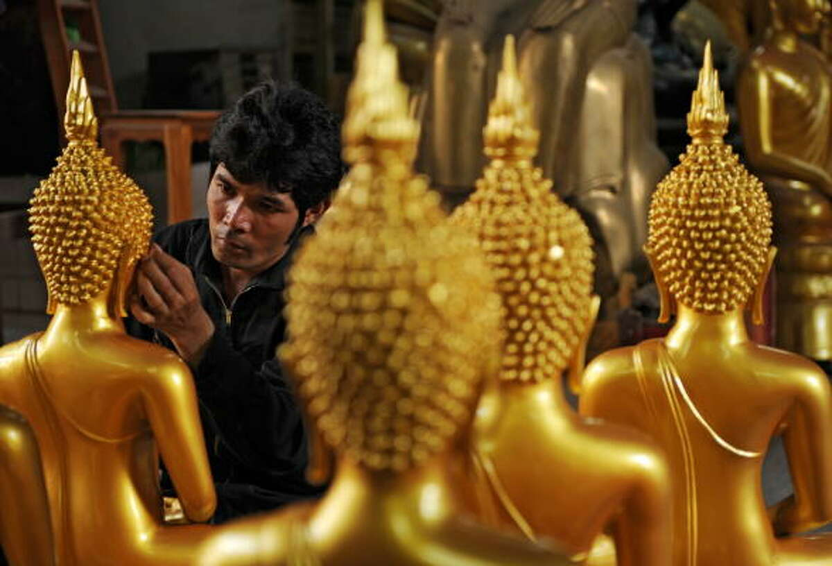 A Thai craftsman puts the finishing touches to a statue of Buddha, at a workshop in Bangkok on May 7, 2009, on the eve of the Wisakha Bucha Day.