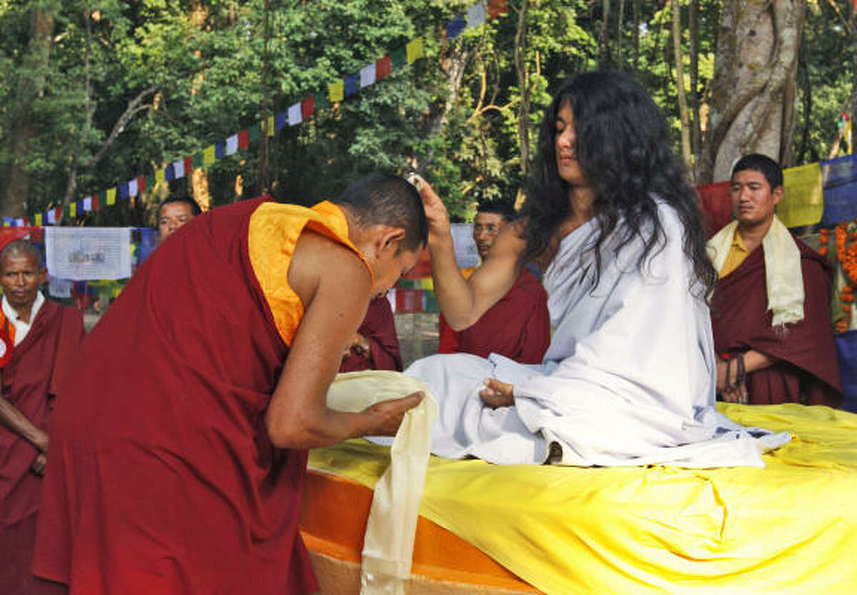 Ram Bahadur Bamjan, in white, believed to be the reincarnation of Buddha, blesses a Buddhist monk in Nijgadh town, about 160 kilometers (100 miles) south of Katmandu, Nepal, Wednesday, Nov. 12, 2008. After retreating into the jungle in southern Nepal for more than a year, Bamjan, 18, re-emerged and began attracting thousands of devotees.